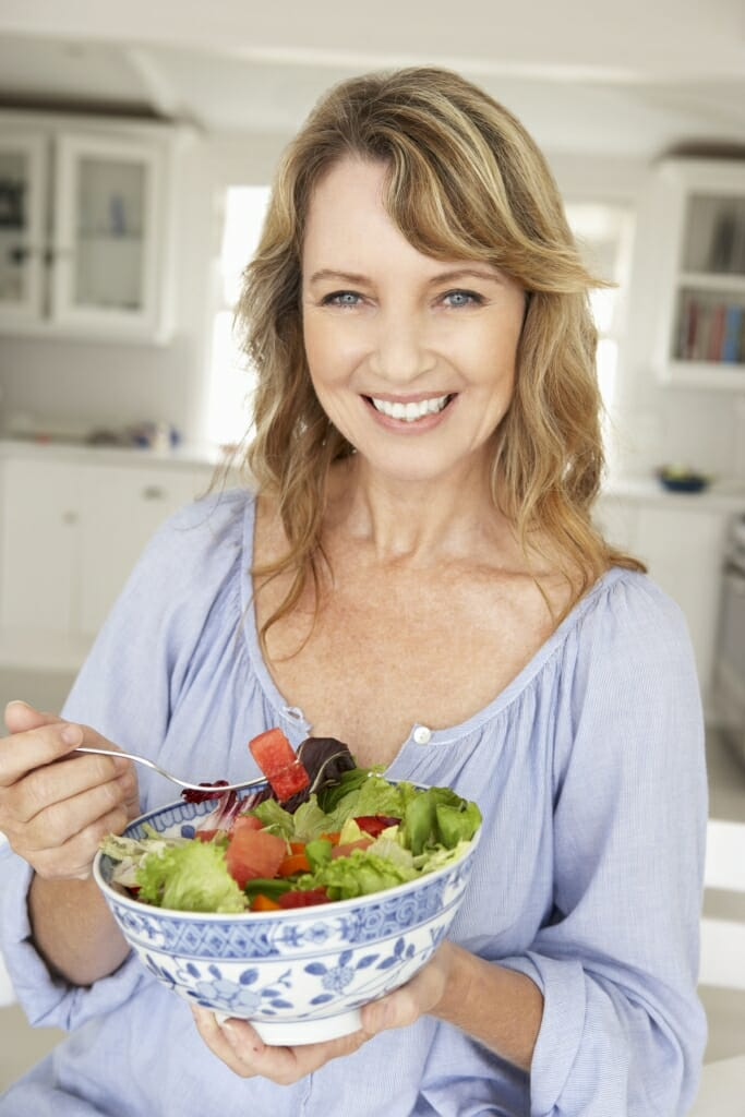 33551887 - mid age woman eating salad