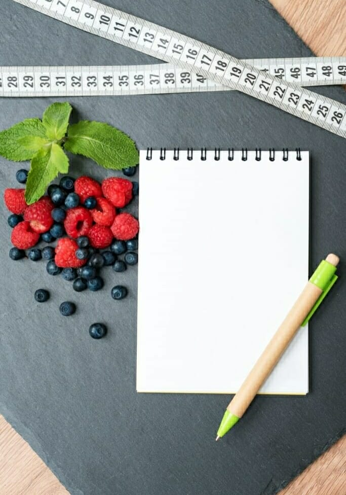 82981004 - blueberries, raspberries, mint, measuring tape and notepad for writing notes or resolutions, concept of sport, diet, slimming, detox, healthy lifestyles and nutrition. mock up, space for text.